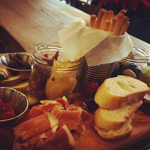 assortment of meats cheese and olives on a wooden board